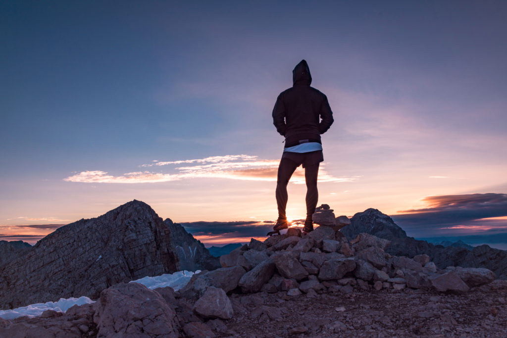 Male hiker in the vast mountain landscape at sunset. Beautiful mountain panorama in the evening in the Alps